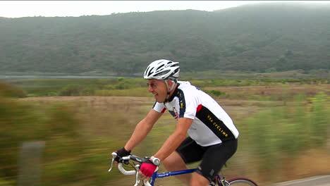 Un-Ciclista-Jadea-Y-Hace-Muecas-Mientras-Camina-Por-Una-Carretera