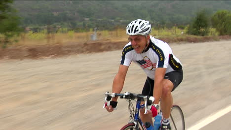 A-bicyclist-smiles-as-he-peddles-along-a-highway-in-a-rural-area