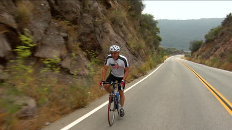 A-bicyclist-peddles-along-a-highway-in-a-mountainous-area