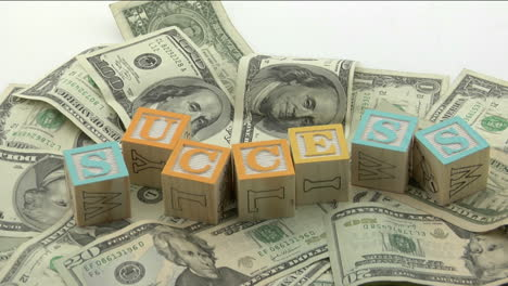 Arranged-wood-blocks-spell-out-the-word-success-on-top-of-a-pile-of-paper-currency