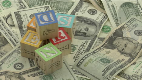 wooden-alphabet-blocks-sit-on-top-of-a-pile-of-money