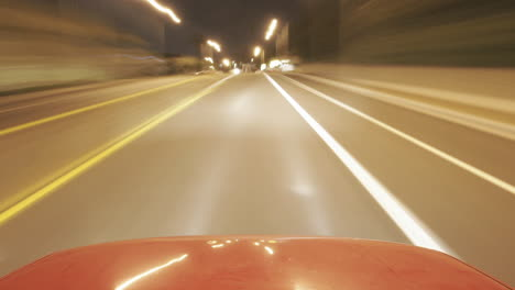 A-shiny-car-travels-on-city-streets-at-night