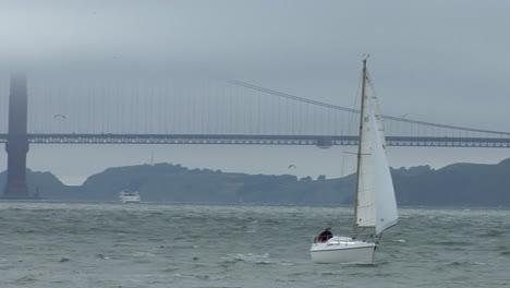 A-sailboat-coasts-near-the-Golden-Gate-Bridge-on-a-windy-day