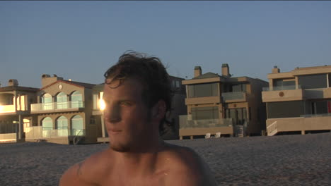 A-man-grabs-his-surfboard-and-runs-towards-the-ocean