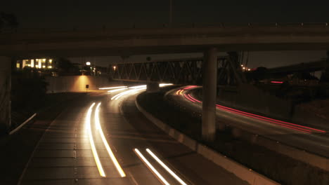 Vehicle-headlights-shine-on-a-freeway-at-night