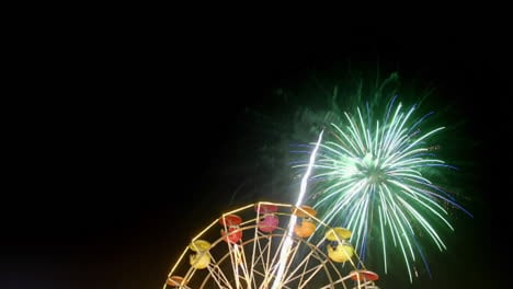 Fireworks-explode-over-a-Ferris-wheel-in-time-lapse