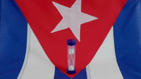 Una-Bandera-Cubana-Se-Sienta-Debajo-De-Un-Reloj-De-Arena