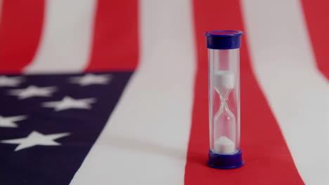 An-American-flag-lies-beneath-a-run-hourglass