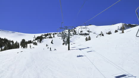 POV-of-someone-riding-up-a-ski-lift-in-the-mountains