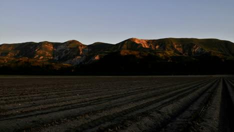 Lapso-De-Tiempo-De-La-Luz-Disminuyendo-En-Algunas-Montañas-Y-Un-Campo-Cuando-El-Sol-Se-Pone