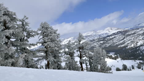 Timelapse-of-clouds-rolling-over-montaña-tops-and-snow-covered-trees