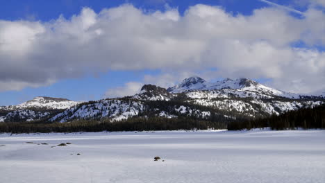 Timelapse-of-clouds-blowing-over-frozen-lake-and-mountains
