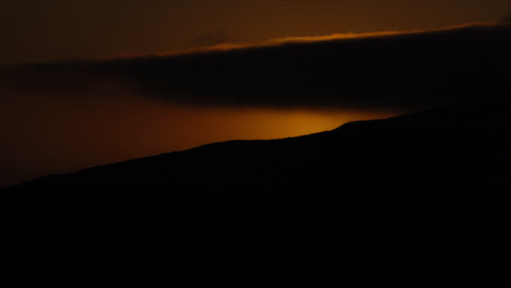Time-lapse-of-sun-disappearing-behind-mountain-top-at-sunset