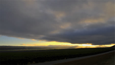 Time-lapse-of-cloudy-sunset-over-a-vineyard