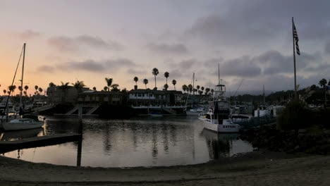 Time-lapse-clouds-at-dusk-blowing-over-channel-lined-with-homes-and-boats