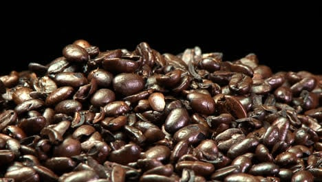 A-pile-of-roasted-coffee-beans-slowly-rotating