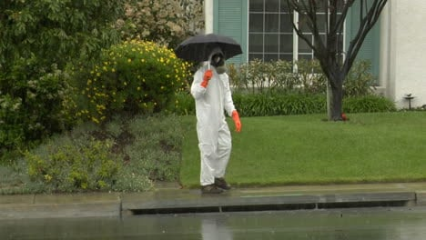 A-man-in-a-hazmat-suit-holds-an-umbrella-and-crosses-the-street