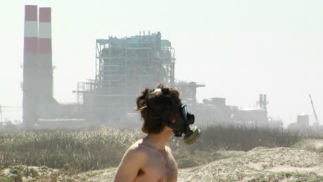 A-man-in-a-gas-mask-stands-in-front-of-a-power-plant