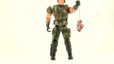 An-Army-action-figure-holds-a-plastic-figurine-of-a-woman-at-a-gas-pump-by-a-string