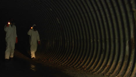 -individuals-wearing-hazmat-suits-use-flashlights-to-inspect-a-dark-tunnel