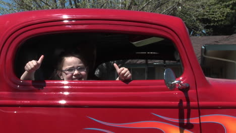 A-young-girl-gives-two-thumbs-up-out-a-car-window