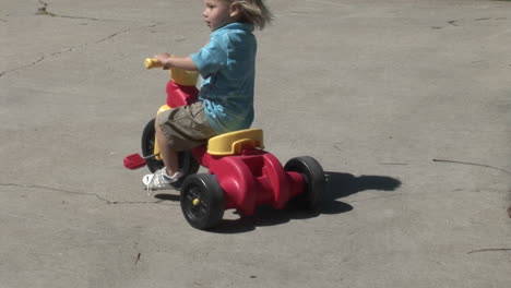 A-young-girl-rides-a-skateboard-and-a-boy-rides-a-plastic-tricycle