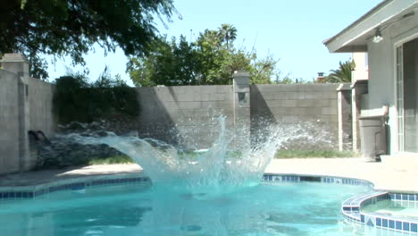 A-man-wearing-fins-and-a-snorkel-jumps-off-of-a-diving-board-into-a-pool