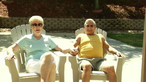 A-husband-and-wife-sit-in-lawn-chairs-holding-hands