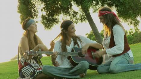 Una-Mujer-Toca-Una-Guitarra-Mientras-Otras-Dos-Juegan-Con-Su-Cabello