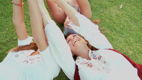Women-lie-on-the-grass-and-give-peace-signs