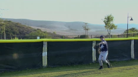A-young-baseball-player-catches-a-ball-as-it-almost-goes-over-the-back-fence