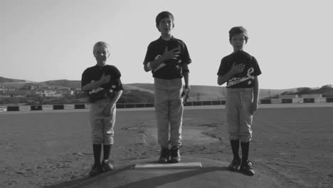 Black-and-white-shot-of-young-baseball-players-cover-their-hearts-with-their-hats