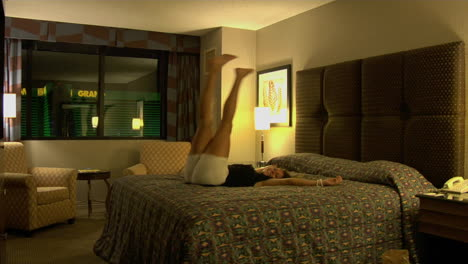 A-young-woman-jumps-backwards-onto-a-hotel-room-bed