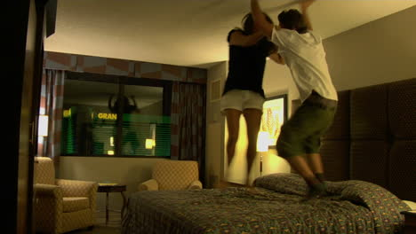A-young-woman-and-man-jump-on-a-hotel-room-bed