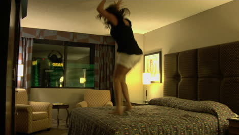A-young-woman-jumps-on-a-hotel-room-bed