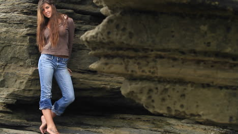 A-young-woman-leans-against-a-rock-wall-