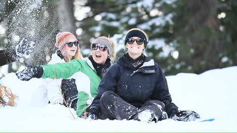 Young-women-on-a-ski-slope-toss-snow-in-the-air