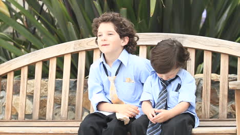 A-pair-of-boys-in-formal-dress-sit-on-a-wooden-bench-
