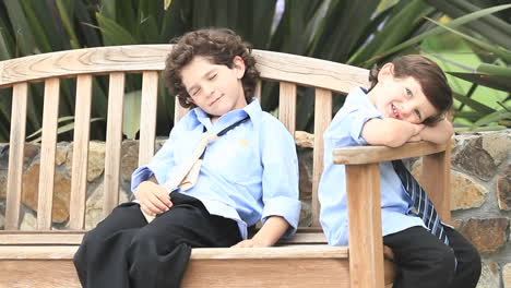 A-pair-of-boys-in-formal-dress-sit-on-a-wooden-bench-1