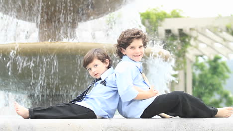A-pair-of-boys-in-formal-dress-sit-back-to-back-in-front-of-a-fountain-