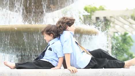 A-pair-of-boys-in-formal-dress-sit-back-to-back-in-front-of-a-fountain-1