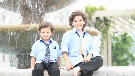 A-pair-of-boys-in-formal-dress-play-in-front-of-a-fountain