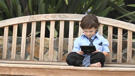 A-boy-in-formal-dress-plays-with-an-electronic-device-on-a-wooden-bench-