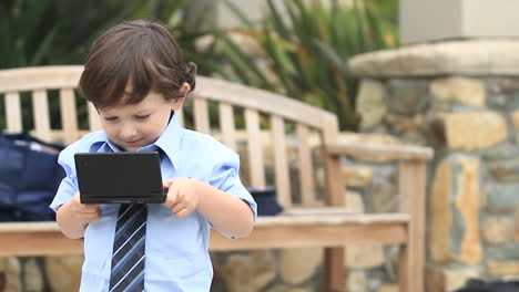 A-boy-in-formal-dress-plays-with-an-electronic-device