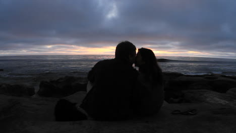 A-couple-kiss-on-a-beach-just-after-sunset-