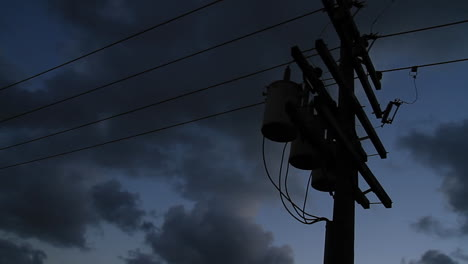 Power-lines-silhouetted-against-a-dark-sky-