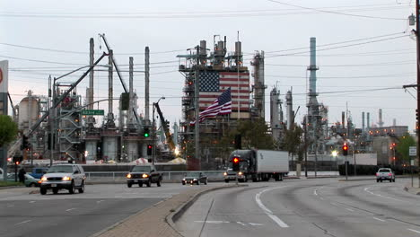 Traffic-passes-by-an-industrial-plant-adorned-with-two-large-American-flags