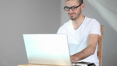 A-young-man-sits-and-smiles-as-he-starts-using-his-laptop-computer