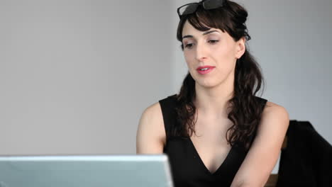 A-woman-focuses-her-attention-between-her-laptop-and-talking-to-someone-in-the-room