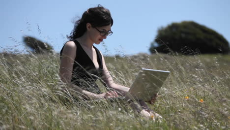 A-woman-sits-in-a-field-using-her-laptop-computer